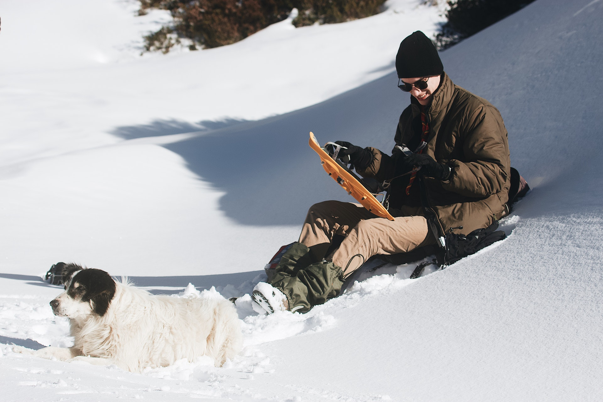 man-in-brown-jacket-and-black-pants-sitting-on-snow-covered-3604947